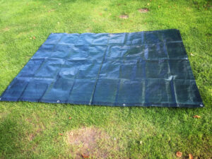 Simply lay the tarp on the ground and set up your bounce house on top of it